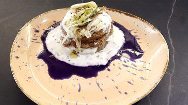 Tortino di patate e lenticchie con colata di panna acida su verza viola liquida